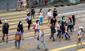 People wearing face masks cross a street in Hong Kong, where 500 new infections have been confirmed in the past fortnight.