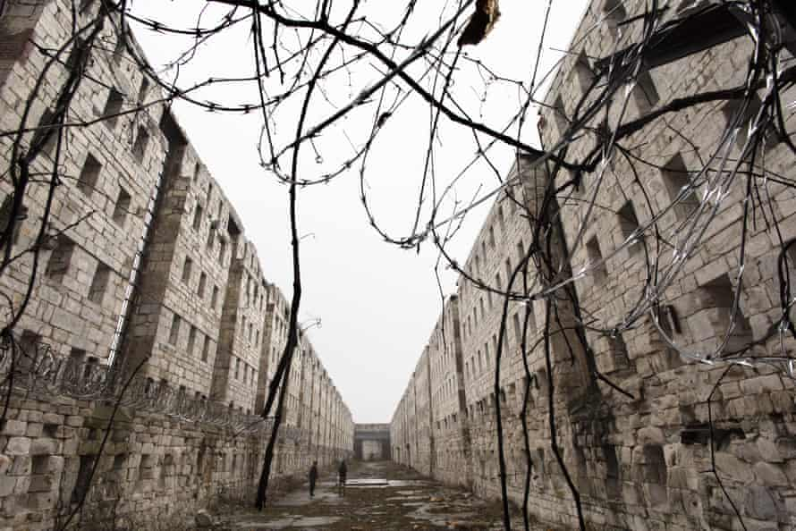 Concertina wire and vines line the stone walls of a former cell block at Sing Sing correctional facility.