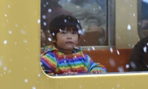 A boy looks at falling snow from a train window in Tokyo.