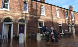 People walk down a flooded street in Carlisle, Cumbria