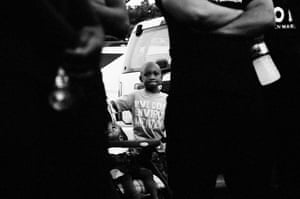 A boy peers out from behind marchers during the 300 Man March in 2013