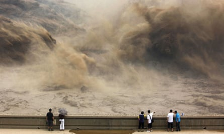 visitors gathering to giant gushes of water released from the Xiaolangdi dam to clear up the sediment-laden Yellow river and to prevent localized flooding, in Jiyuan, central China