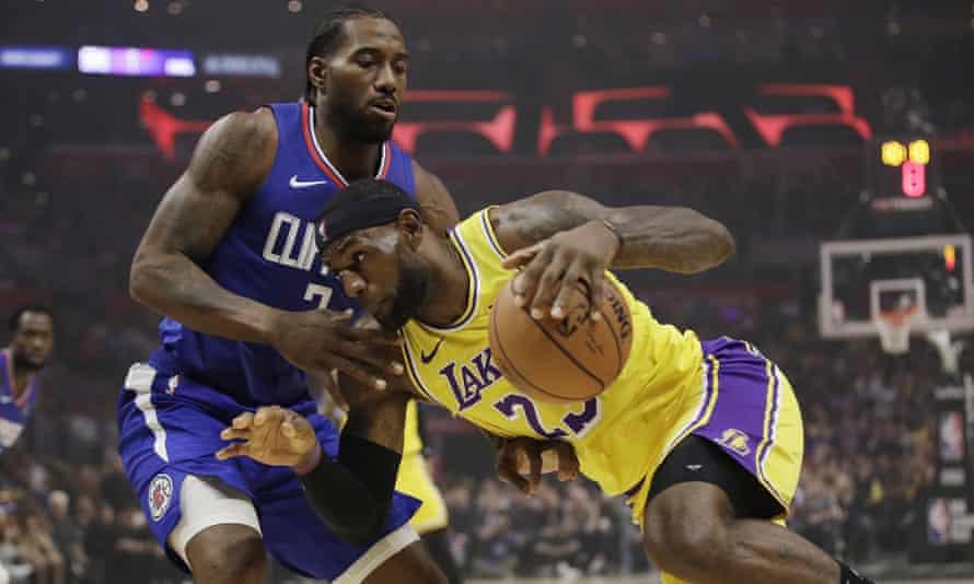 LeBron James, and Kawhi Leonard compete for the ball during their teams' season opener