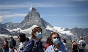 Tourists wearing protective face masks at the Gornergrat rocky ridge above the resort of Zermatt in Switzerland.