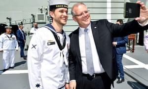 Scott Morrison with a navy personnel onboard HMAS Brisbane, which was commissioned on Saturday.