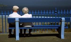 an elderly couple sit on a bench