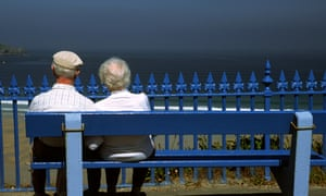 Retired couple on bench overlooking the sea
