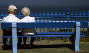 A retired couple sit on bench overlooking the sea.