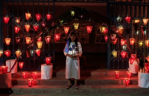 A girl poses for a photo during the Lantern festival, celebrating the eve of the Virgin Mary's birth.