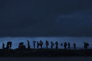 Rohingya refugees walk across Paddy fields at dusk after crossing the border from Myanmar