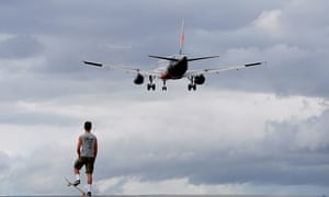guy on a skateboard watches a plane take off