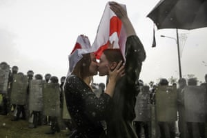 Two women kiss under flag