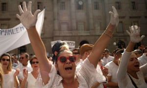 People raise hands painted in white at a rally to call for dialogue between Catalonia and Madrid.