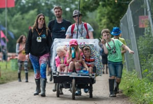 Festivalgoers including several young children arrive at Glastonbury