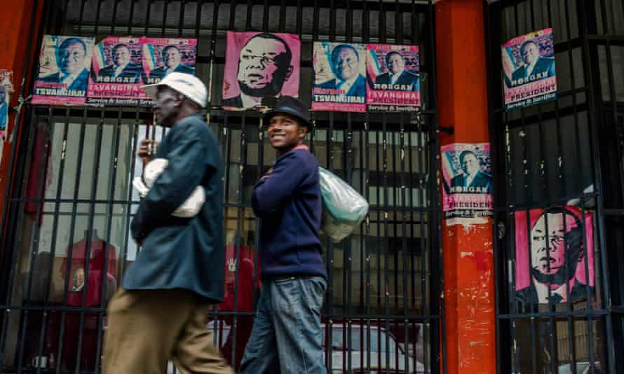 Harare residents walk past campaign posters portraying Zimbabwe's opposition leader Morgan Tsvangirai on Wednesday.