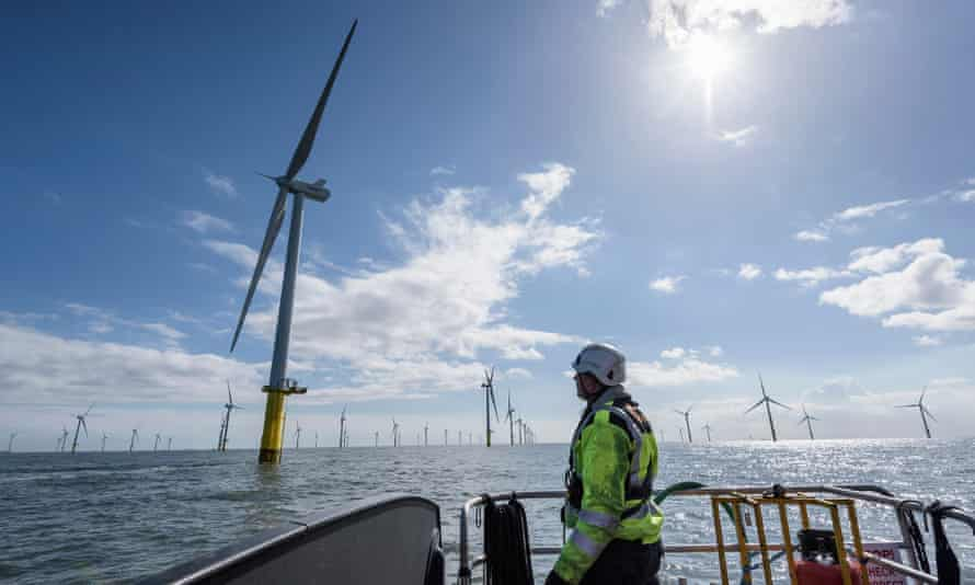 A worker in a hard hat at the bow of a ship looks up at the nearest of dozens of huge wind turbines arranged in rows in the sea