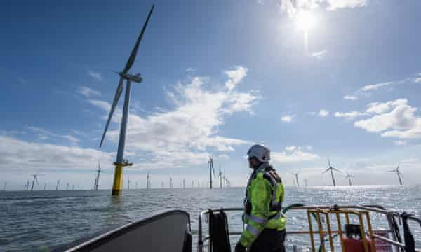 Worker looking out from ship to offshore wind farmEngineer with Wind Turbines in the sea UK