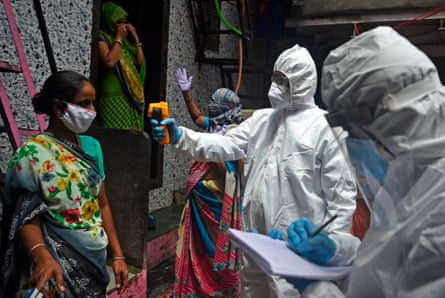 Medical volunteers take the temperature of a woman during door-to-door medical screening inside Dharavi, in Mumbai.