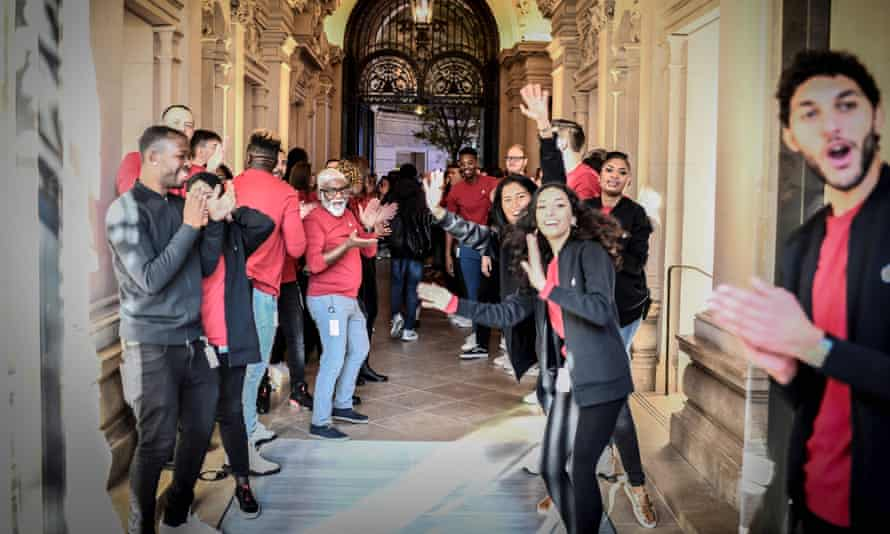 Apple employees clap to welcome customers at the new Apple store in Paris.