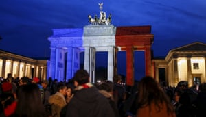 People stand in front of the Brandenburg gate illuminated in the colours of the French flag.