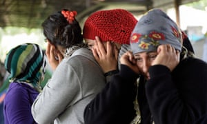 Refugee women cover their ears as they hear military jet planes flying over the makeshift camp at the Greek-Macedonian border near the village of Idomeni during a military drill, on April 14, 2016.