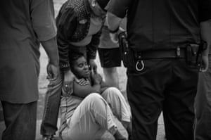 A woman slumps to the ground after hearing that a man shot was not her son