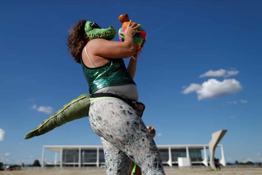 A demonstrator dressed in an alligator costume dances during a protest calling for access to the coronavirus vaccine and against Brazilian President Jair Bolsonaro.