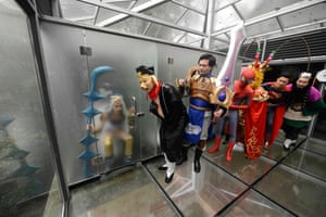Cosplay actors pose for photos in a glass public toilet to mark World Toilet Day in Changsha