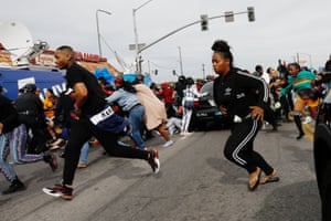People run away from a stampede as LAPD officers reopen a path for the funeral procession of rapper Nipsey Hussle.