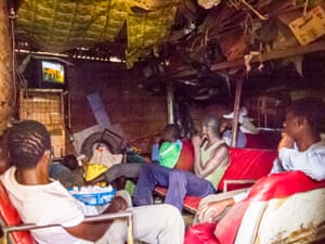 Peanut seller takes a break in a repurposed storage room, Kibera.