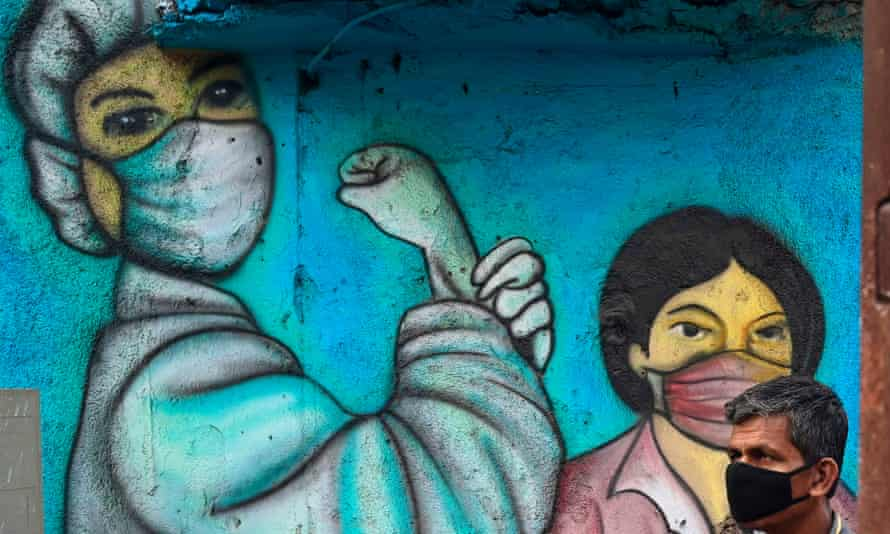 A commuter walks past a mural depicting Covid frontline workers, Mumbai, January