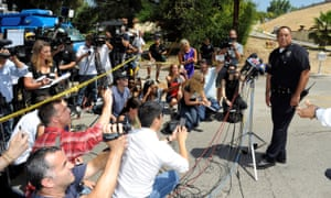 A Los Angeles police department representative briefs the media as they wait outside the home of singer Chris Brown Tuesday in California.