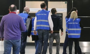 Airport staff walk to a non-public area with people who waited for the Germanwings flight from Barcelona