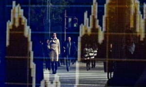 Pedestrians are reflected in a stock market indicator board in Tokyo, Japan