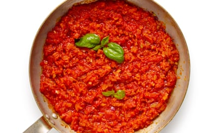 A mixed sauce of tomatoes and basil mashed together in a pan.