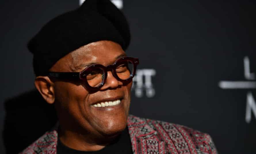 Samuel L. Jackson in dark, heavy-rimmed glasses and hat, smiling