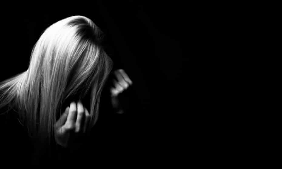 Black and white photo of blonde women in the dark with hands over face.