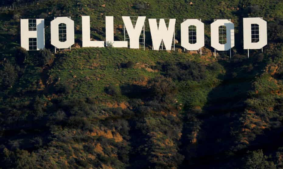 The iconic Hollywood sign is shown on a hillside above a neighborhood in Los Angeles.