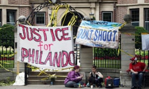 Banners block the entrance gate as demonstrators gather outside the governor's residence in St Paul, Minnesota, on Friday.