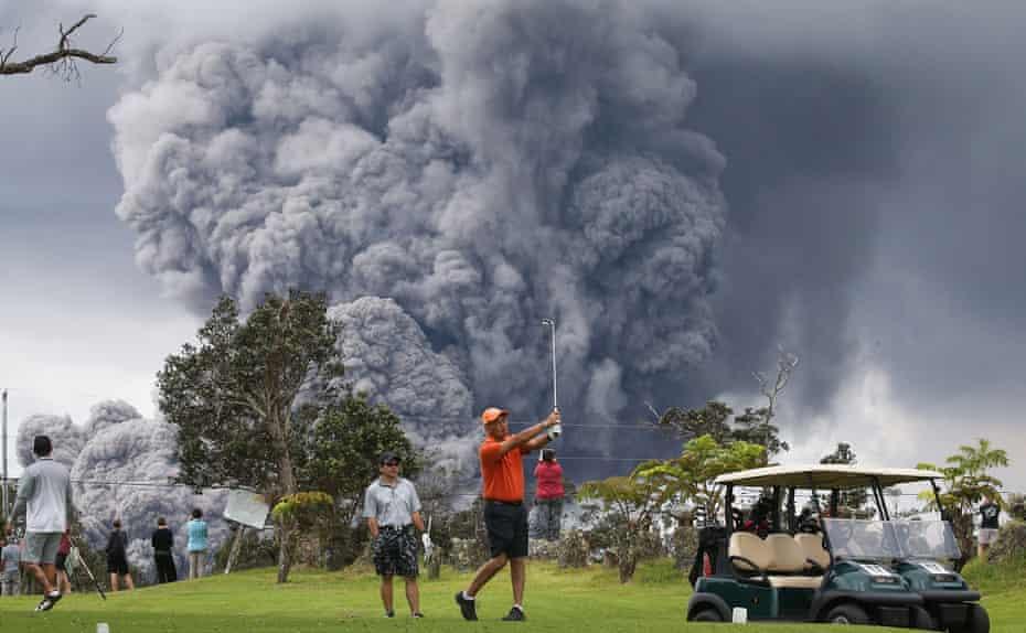 Golfers ignore an erupting volcano, Hawaii