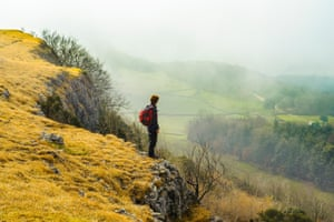 Walker overlooks a misty Lyth Valley from the ridge of Scout Scar in the Lake District National Park Cumbria