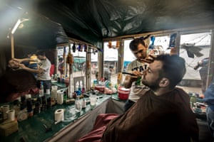 Calais, France<br>A migrant shaves another in his makeshift hairdressing salon in the The Jungle