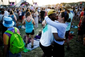 A couple embrace as the sun sets behind the Pyramid stage