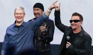 tim cook touching fingers with Bono
