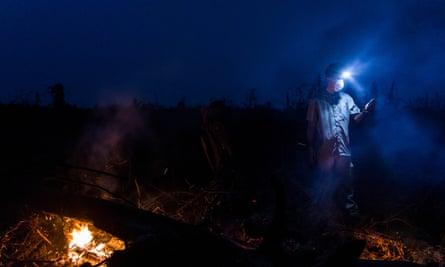 A Greenpeace investigator captures GPS coordinates beside the burning remains of recently cleared peatland orangutan habitat