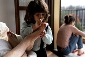 San Fiorano, Italy. Schoolteacher Marzio Toniolo's two-year-old daughter Bianca paints his toenails as they while away time at home in one of the original 'red zone' towns in Lombardy. His wife, Bianca's mother, Chiara Zuddas looks out from their balcony