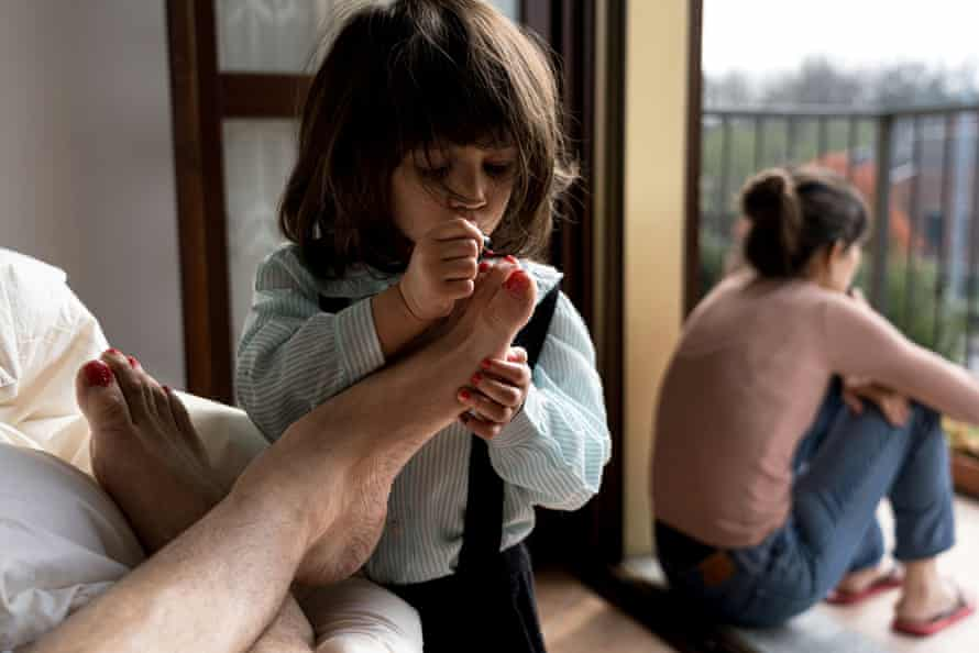 A daughter paints her father's toenails while her mother looks out of a balcony