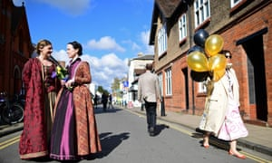 Two women in costume talk as they prepare for the parade