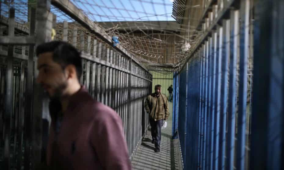 Palestinians cross through Israeli checkpoint to get to work.