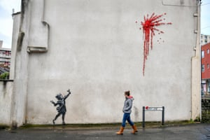 Bristol, UK. A new work, thought to be by Banksy, has appeared on the side of a house in the Barton Hill area of the city. The black and white stencil of a girl with a catapult and the paint splat, made of plastic flowers, has yet to be confirmed as being the work of the artist